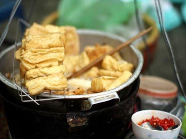 Từng miếng đậu dài được xếp đều san sát nhau ngập chảo dầu đang sôi sùng sục mỡ chín vàng.