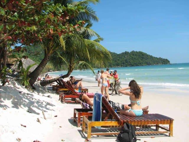 Du khách nằm phơi nắng trên những chiếc ghế dài đặt bên bờ biển