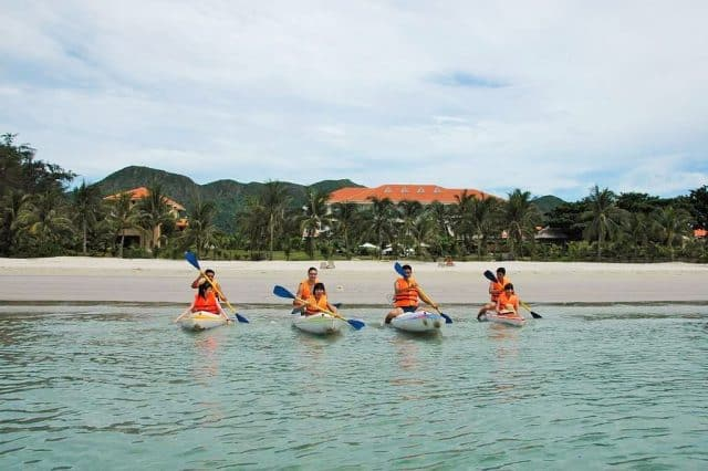 Du khách tham gia trải nghiệm chèo thuyền Kayak tại khu vực bãi tắm riêng của resort